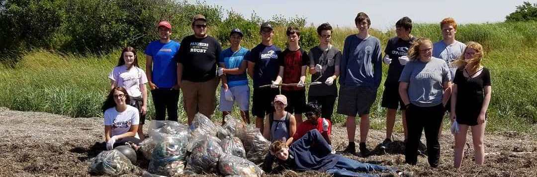 Group photo of individuals with results of beach cleanup